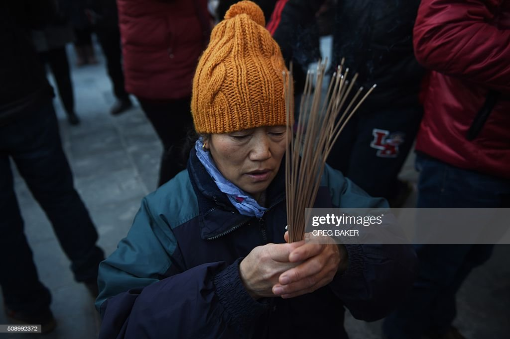 A woman burns incense and prays for good luck at the Yonghegong Lama Temple on the first day of the Lunar New Year in Beijing on February 8, 2016. Millions of Chinese began celebrating the 'Spring Festival', the most important holiday on the Chinese calendar, which this year marks the beginning of the Year of the Monkey. AFP PHOTO / GREG BAKER / AFP / GREG BAKER