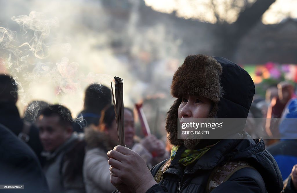 A woman burns incense for good luck at the Yonghegong Lama Temple on the first day of the Lunar New Year in Beijing on February 8, 2016. Millions of Chinese began celebrating the 'Spring Festival', the most important holiday on the Chinese calendar, which this year marks the beginning of the Year of the Monkey. AFP PHOTO / GREG BAKER / AFP / GREG BAKER