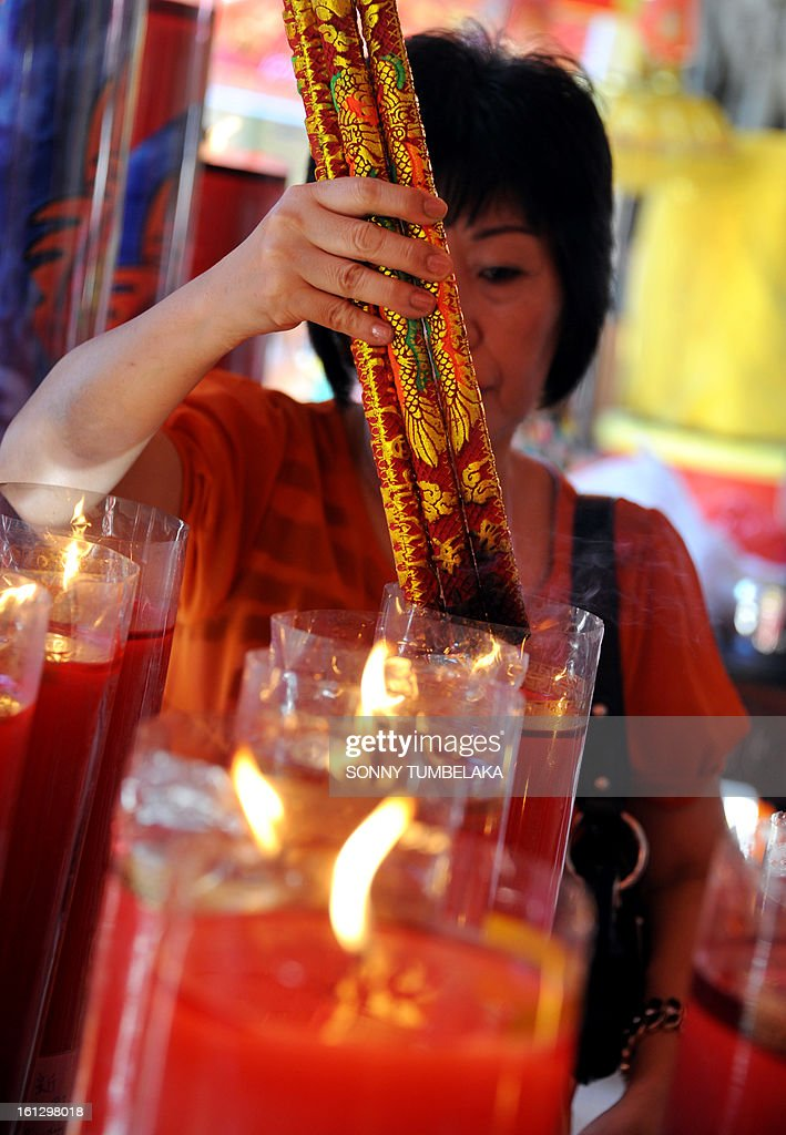 A woman burns incense sticks before praying to celebrate the Chinese Lunar New Year of the Snake at a Dharmayana temple in Kuta on Indonesia's resort island of Bali on January 10, 2013. Lunar New Year is celebrated in many parts of the predominantly Islamic country of 240 million people where Chinese heritage took roots through ancient transmigration. AFP PHOTO / Sonny TUMBELAKA