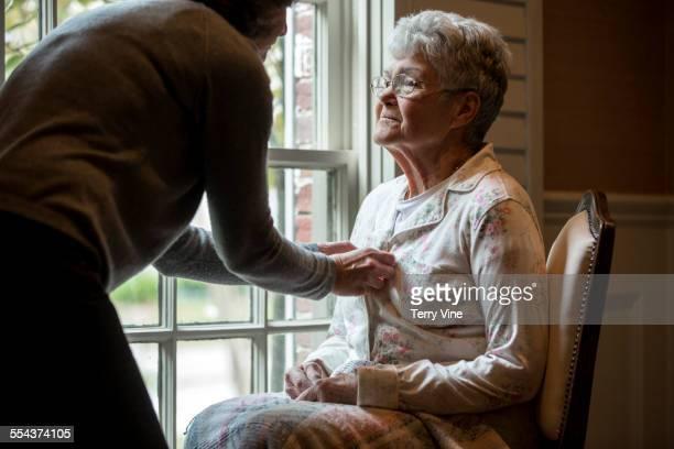 Woman buttoning pajamas of mother near window