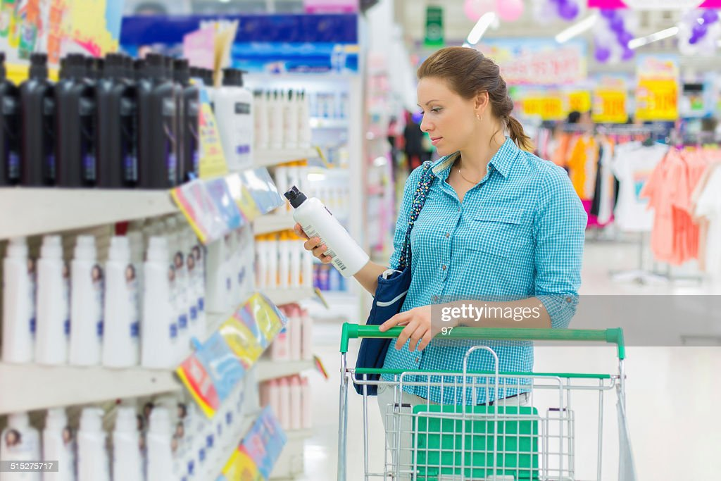 woman buy shampoo in the supermarket