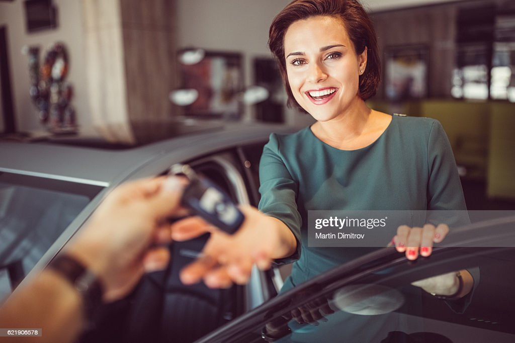 Woman buying a new car : Stock Photo