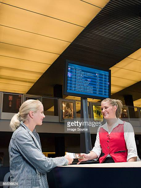 A woman buying a ticket from the box office
