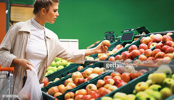 Woman buying apples at a supermarket.