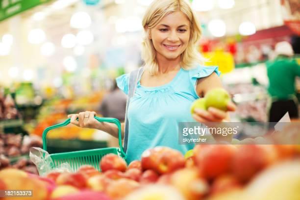 Femme acheter des pommes dans le magasin de fruits.