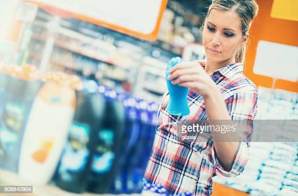 Woman buying cosmetics in supermarket.