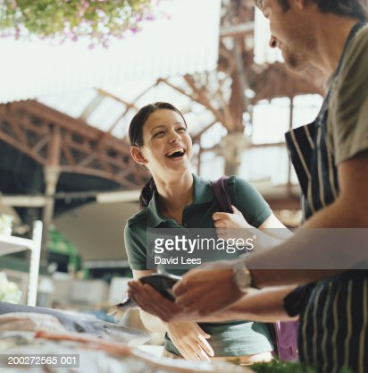 Woman buying fish from fishmonger in market, smiling (focus on woman)