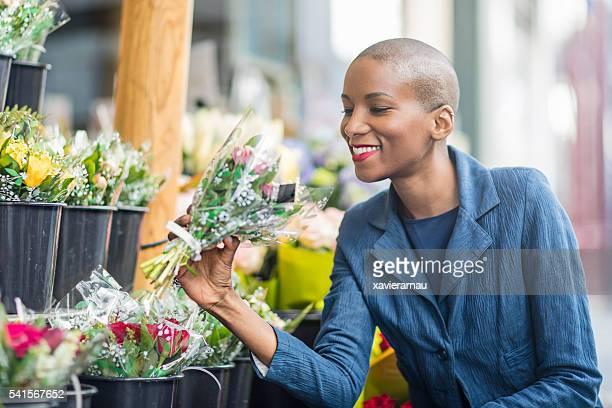 Femme, achat de fleurs dans une épicerie à Paris