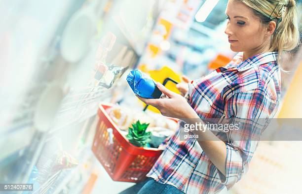 Woman buying food in supermarket.