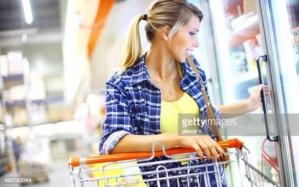 Woman buying frozen food in supermarket.