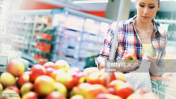 Woman buying fruit in supermarket.