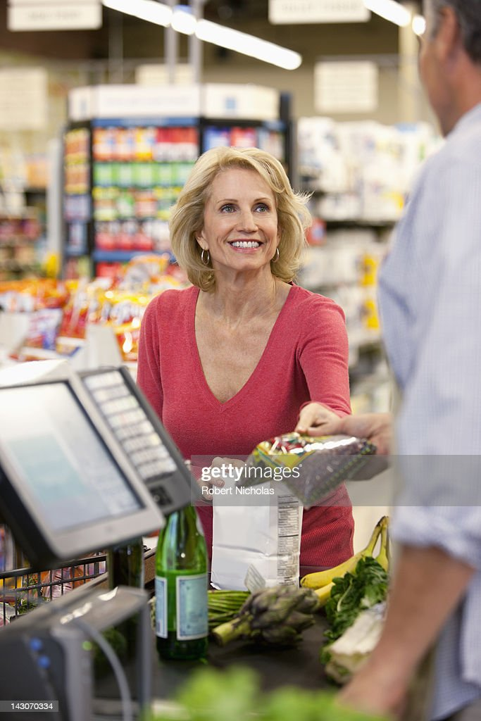 Woman buying groceries at supermarket : Stock Photo
