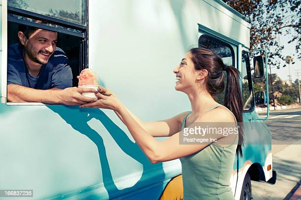 Woman buying ice cream from truck