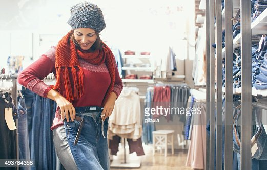 Woman buying jeans at retail store.