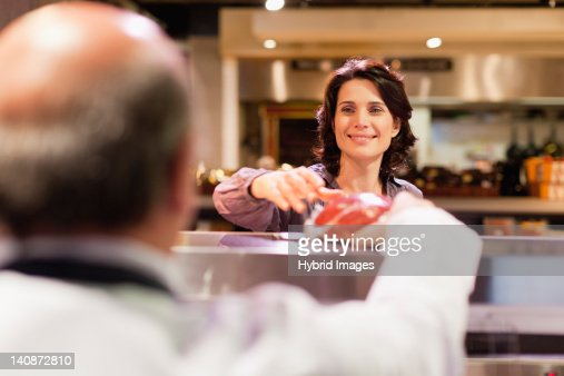 Woman buying meat from butcher : Stock Photo