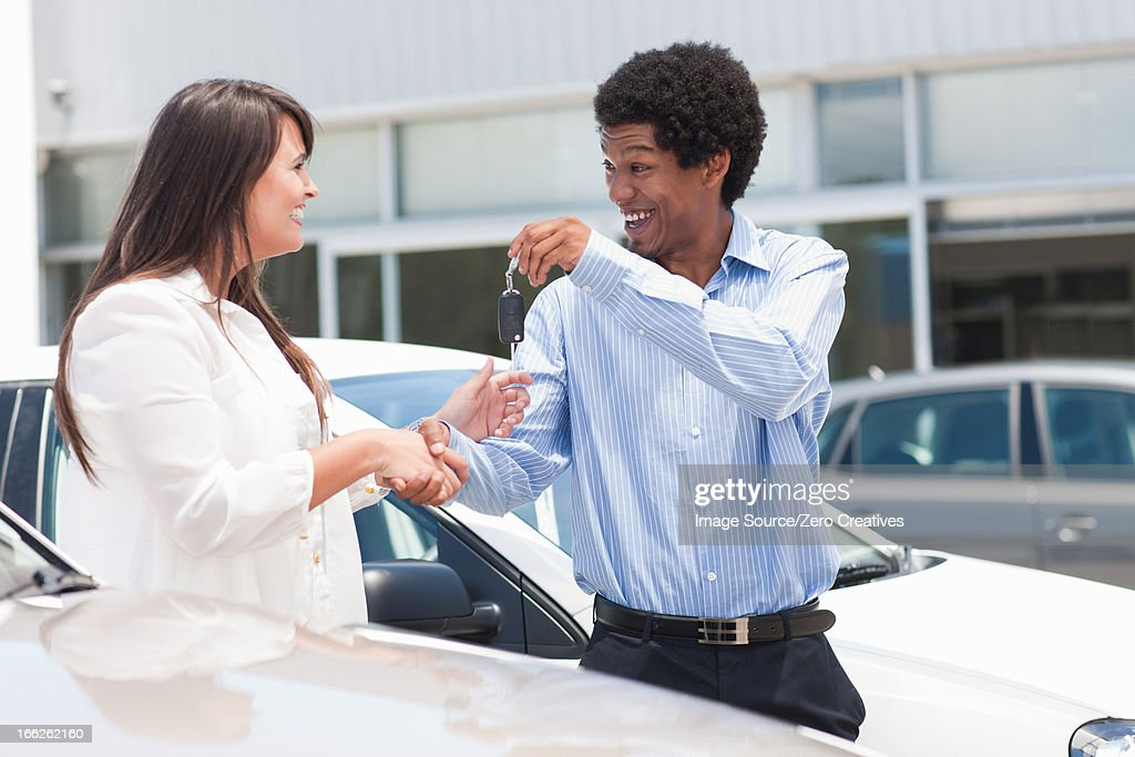 Woman buying new car from salesman : Stock Photo