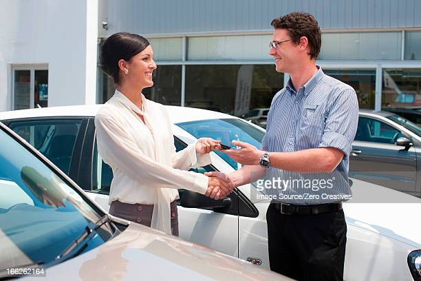 Woman buying new car from salesman