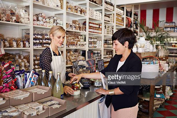 Woman buying olives and cheese at deli shop