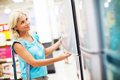 Woman buying refrigerator in a store.