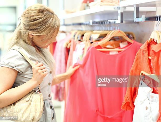 Woman buying shirt in shopping mall.