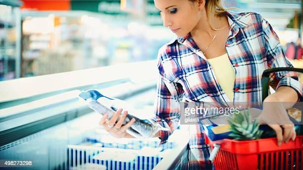 Mulher comprar alguns os alimentos congelados no supermercado.