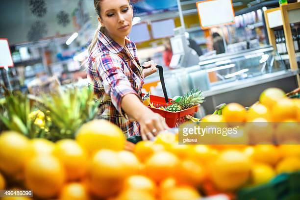 女性のスーパーで購入するいくつかのフルーツます。