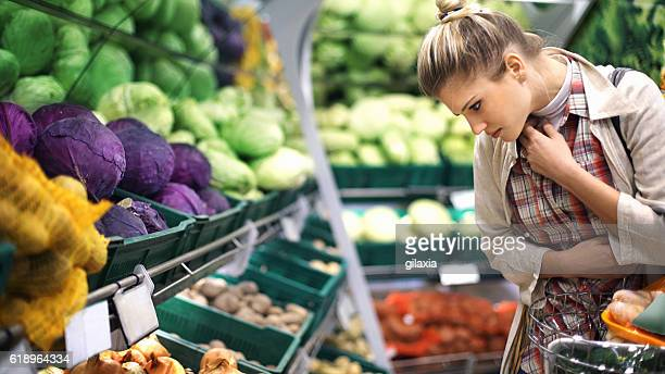 Woman buying vegetables at a supermarket.