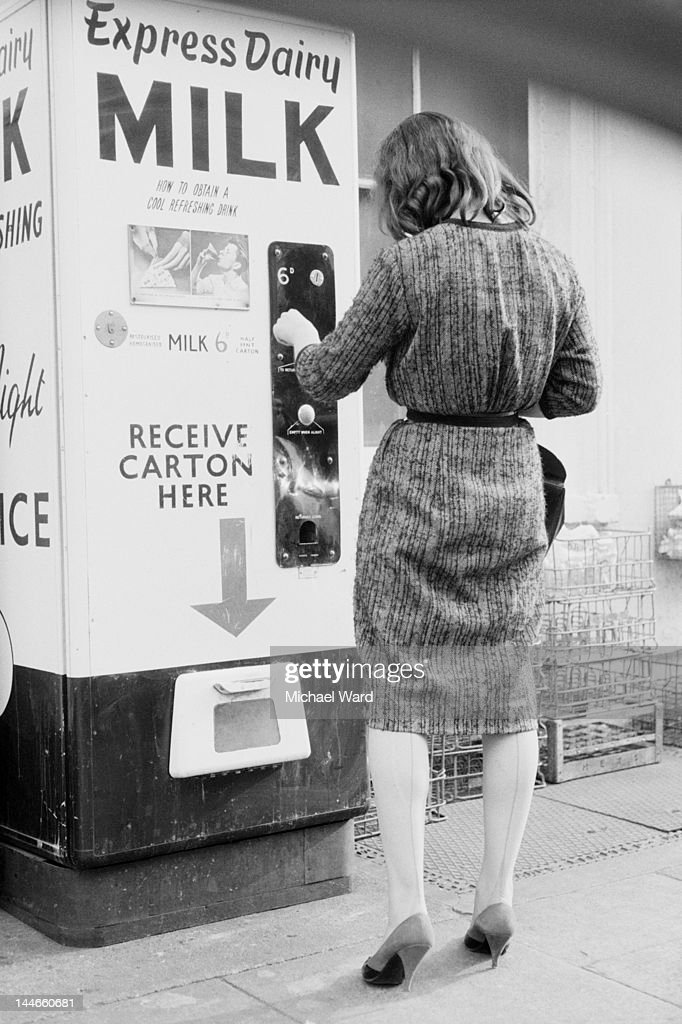 A woman buys a carton of milk from a vending machine, UK, May 1960.