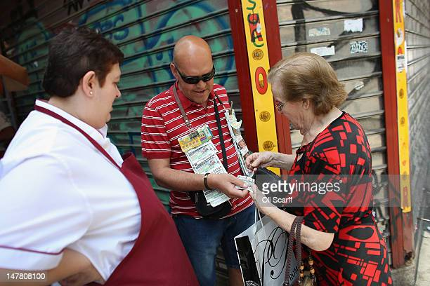 A woman buys a lottery ticket from a street vendor on July 3 2012 in Madrid Spain Despite having the fourth largest economy in the Eurozone the...