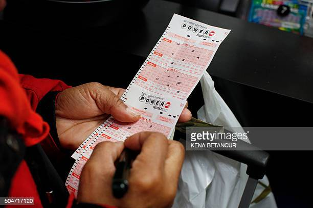 A woman buys a Powerball lottery ticket at a newsstand in New York City on January 12 2016 Record sales drove up the largest jackpot in US history to...
