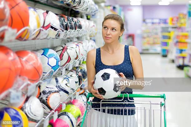 Frau kauft einen Fußball-Spielball