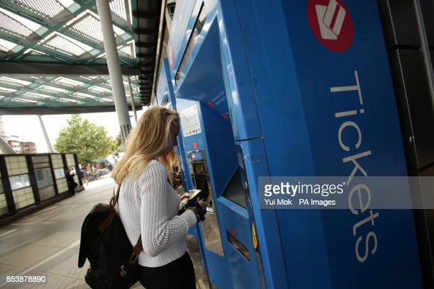 A woman buys a train ticket from a machine at Finsbury Park station in north London as rail passengers will today learn just how much their season...