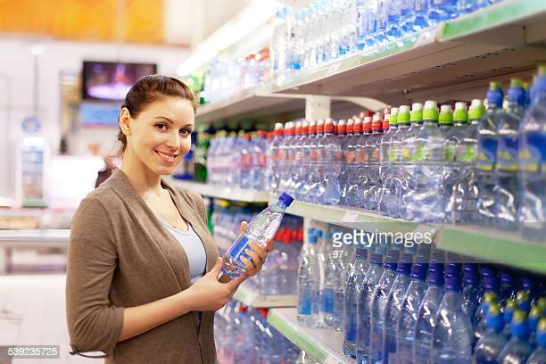 woman buys a water bottle in shop