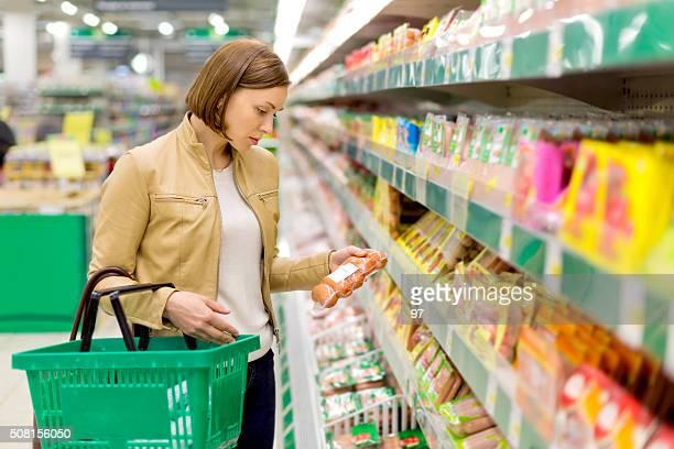 Mujer de compras en el supermercado salchicha hervido