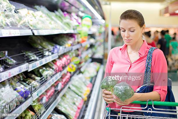 woman buys broccoli