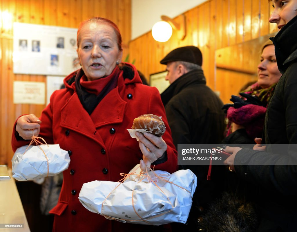 A woman buys cakes at a popular sweet shop in Warsaw including jam-filled doughnut Paczki traditionally eaten on the Thursday of Carnival, the Fat Thursday on February 7, 2013.