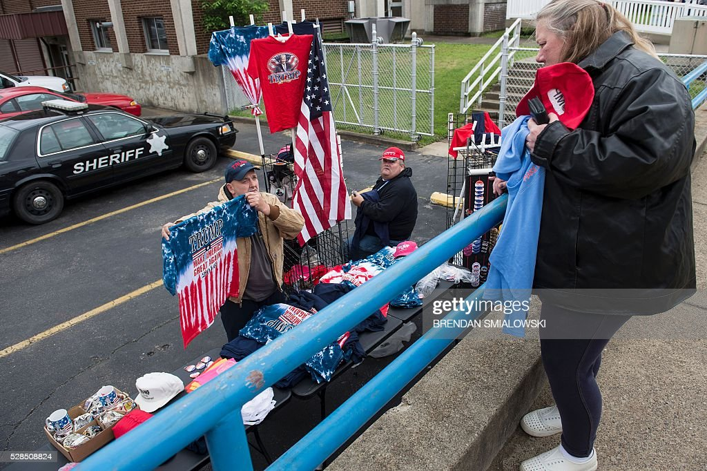 A woman buys campaign clothing before a rally for Republican US Presidential hopeful Donald Trump in Charleston, West Virginia on May 5, 2016. It's the paradox of the 2016 US presidential elections: Hillary Clinton and Donald Trump are virtually assured of facing off against each other in November, and yet both are widely unpopular. / AFP / Brendan Smialowski