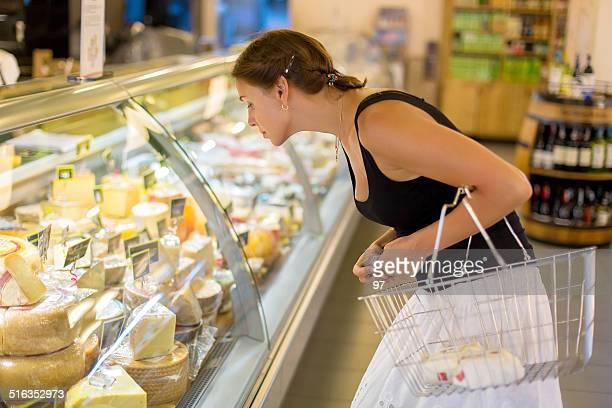 Femme achète fromage dans le supermarché