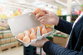 Woman buys eggs in the supermarket. Egg store supermarket price expensive grocery shop concept