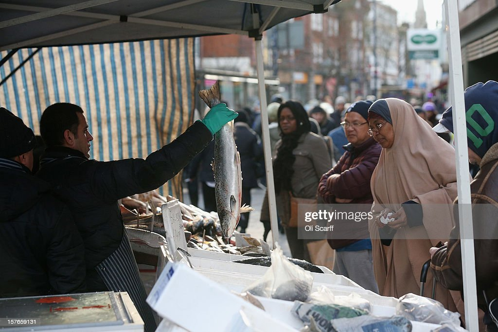 A woman buys fish from a market stall on Lewisham high street on December 5, 2012 in London, England. The Chancellor of the Exchequer George Osborne has stated that the United Kingdom's economy is still struggling during his autumn budget statement to Parliament.