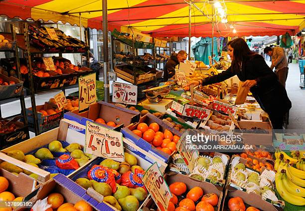 A woman buys fruit from a stall in a Soho market in London on January 25 2012 Britain's economy shrank by more than expected in the fourth quarter...