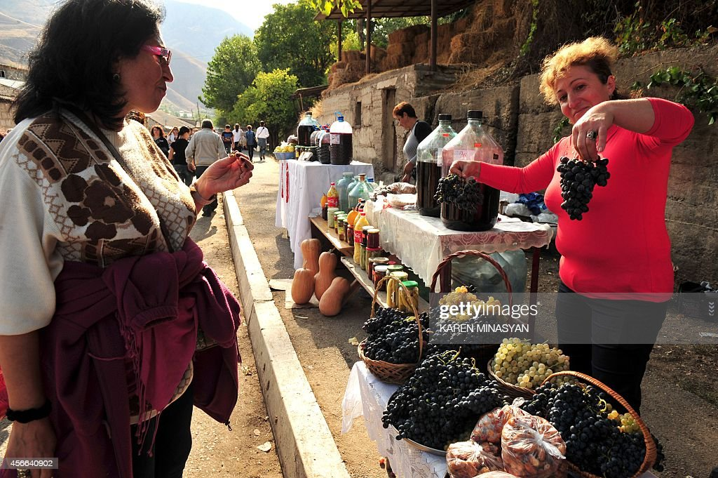 A woman buys grapes at a street market during a wine festival devoted to grapegathering in the village of Areni on October 4 2014 AFP PHOTO / KAREN...