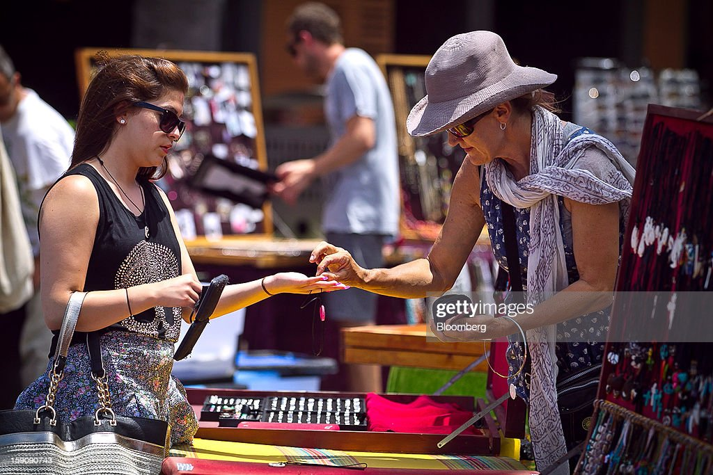 A woman buys jewelry at a market stall at Bondi Beach in Sydney, Australia, on Monday, Jan. 7, 2013. The Bureau of Statistics is scheduled to release retail sales data on Jan. 9. Photographer: Ian Waldie/Bloomberg via Getty Images