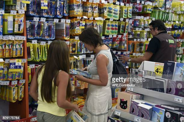 A woman buys school supplies with her daughter at a supermarket on August 18 2015 in LuclaPrimaube near Rodez ahead of the start of the new school...