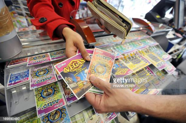 A woman buys scratchcards of the Française des Jeux the operator of France's national lottery and scratchcards from a tobacconists on May 28 2013 in...