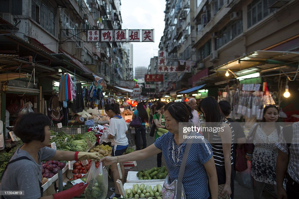 A woman buys vegetables at a market in the Yau Ma Tei district of Hong Kong, China, on Saturday, June 29, 2013. Hong Kongs best-selling newspapers called on readers to join a march to mark the anniversary of the citys handover to China, saying the government has failed to address issues of poverty and universal suffrage. Photographer: Jerome Favre/Bloomberg via Getty Images