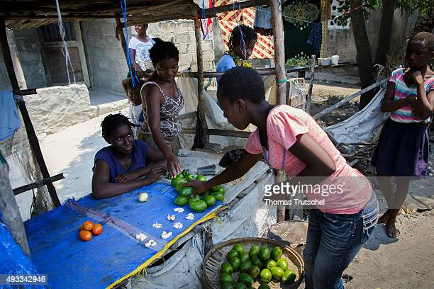 A woman buys vegetables at a vegetable stall in a slum in the city of Beira on September 28 2015 in Beira Mozambique
