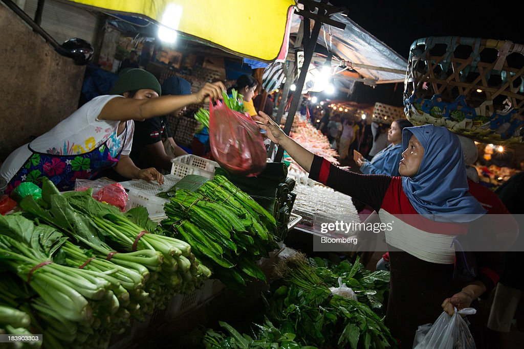 A woman buys vegetables at the Pasar Badung market in Denpasar, Bali, Indonesia, on Tuesday, Oct. 8, 2013. Bank Indonesia said it will regulate currency hedging by individuals and companies, including state-owned firms, to help stabilize Asias most-volatile currency. Photographer: SeongJoon Cho/Bloomberg via Getty Images