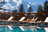 femme allongée au bord d'une piscine au soleil à la neige