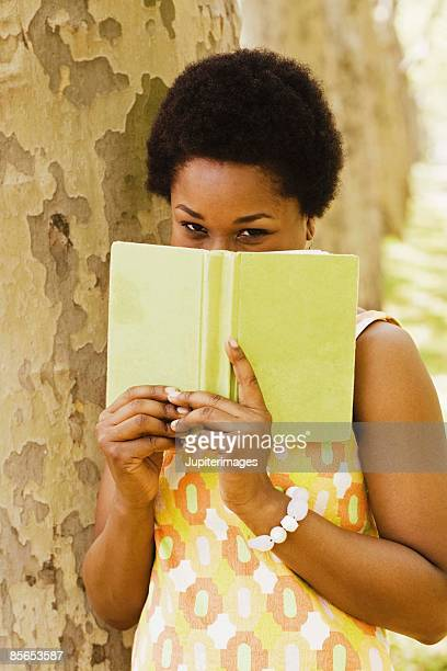 Woman by a tree hiding behind a book